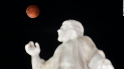 The moon is pictured over the El Salvador del Mundo Monument in San Salvador, El Salvador on April 15, 2014 as a lunar eclipse begins across the Americas. The entire event was to be visible from North and South America, but sky watchers in northern and and eastern Europe, eastern Africa, the Middle East and Central Asia were out of luck, according to US space agency NASA. AFP PHOTO/ Jose CABEZAS        (Photo credit should read JOSE CABEZAS/AFP/Getty Images)